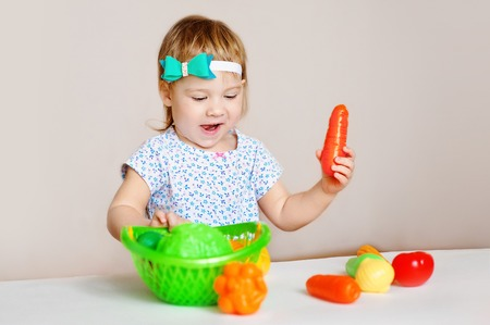 Little girl playing indoors at home or kindergarten. Adorable smiling little child cutting plastic vegetables. Healthy lifestyle for kids. Stock Photo