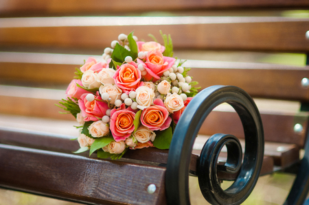 arm bouquet: Wedding bouquet with roses on a wooden bench