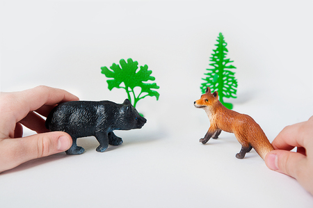 stuff toy: Childs hands are playing with forest animal figures on a white background