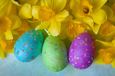 Daffodils And Colorful Decorated Eggs On Sunny Meadow - Easter Holiday Background Stock Photo
