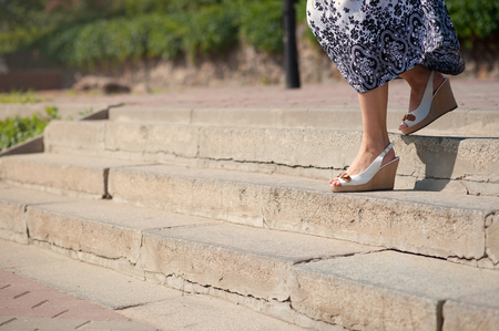 Female feet in sandals on the top of big steps down. Long pathway downstairs 版權商用圖片 - 75862688
