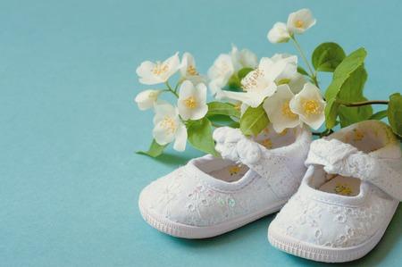 Zapatos de bebé infantiles lindos, blancos del vintage con las flores de la primavera en fondo ciánico y sitio o espacio para la copia, texto, sus palabras. Concepto de un recién nacido, bautizo