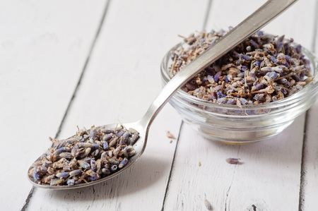 Lavender essential oil ingredients. Wooden spoon full of dry lavender seeds and bunch of dried lavender flowers with aromatherapy oil in small transparent bowl. Relaxing and calming body spa. Stock Photo
