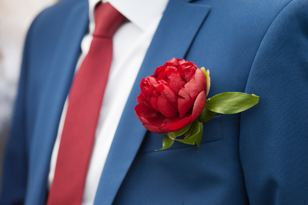 Simple wedding boutonniere on a grey suit, shot outdoors with slight filter effect.
