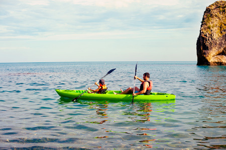lifevest: Two people - an adult and a child father and son in life jackets sail on inflatable boats during hike at summer