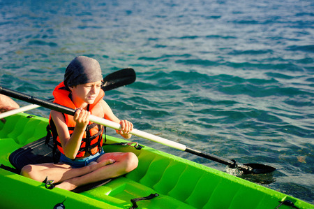 lifevest: A teenage boy paddling a kayak on a lake. There is a fishing pole in the kayak with him.