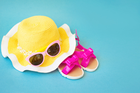 woman sandals: Summer accessories for modern woman on her vacation. Top view. blue background with copy space.
