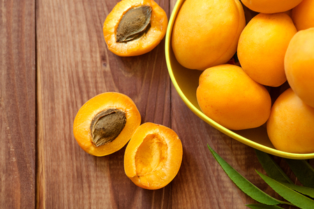 microelements: Apricot. Organic fruits with leaf on wooden background Stock Photo