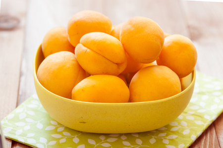 microelements: Heap of apricots in wooden bowl on table Stock Photo
