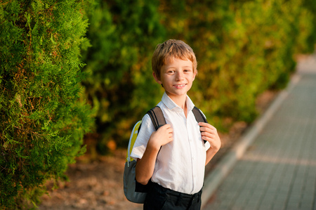 A little boy with a backpack goes on his way to school.