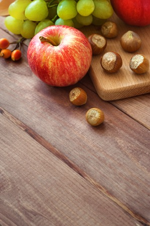 still life with fruit. plums, apples, pears and dry autumn leaves on wooden background. autumn harvest fruit. Soft focus