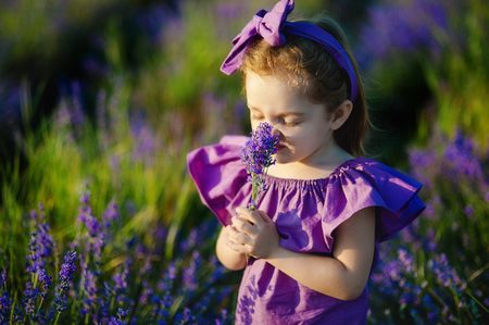 Little girl sniffing the scent of blue flower Stock Photo