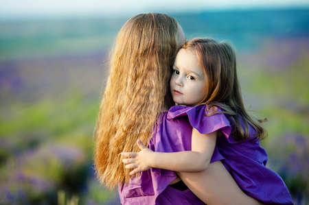 Close up of loving mother and baby posing in flowering field Stockfoto