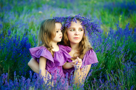 Portrait of beautiful young woman and her little daughter outdoor