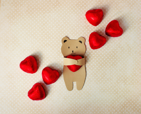 congratulations on the Valentines Day. A small bear of kraft paper holds in his paws a chocolate candy in the form of a heart in a red foil