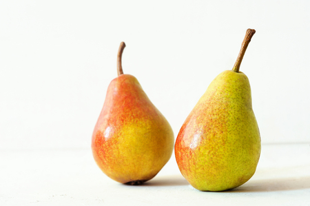 Two ripe red yellow pear fruits on white background