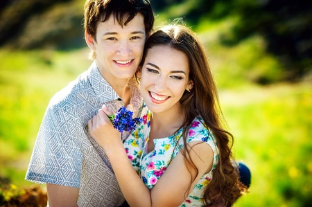 Love story of the beautiful young man and woman. embrace on a nature walk