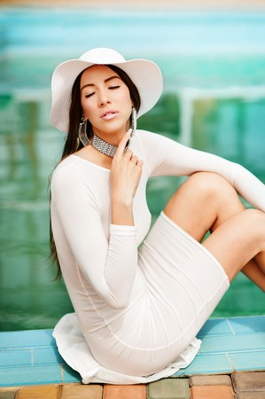 Portrait young dreamy girl with closed eyes in a stylish hat and a tight white dress sitting barefoot under rays of summer sun near the swimming pool
