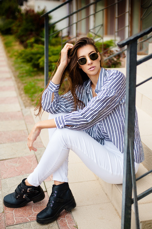 Attractive girl in glasses is posing. She wears a striped shirt, white pants and a black boots. Woman looks into the camera.