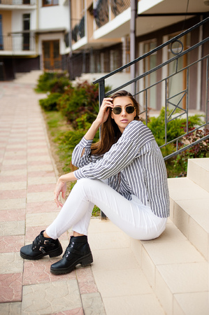 Outdoor portrait of young beautiful girl posing in street. Model wearing stylish sunglasses, stripped black-white blouse. City lifestyle, female fashion concept. Copy, empty space for text Stockfoto