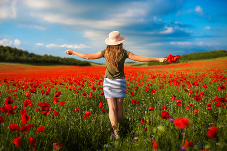 Portrait of beautiful young woman in the field of red poppies