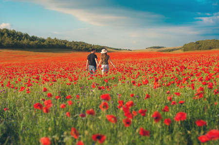 Summer holidays, love, romance and people concept. Happy young hippie couple holding hands and waving to blue sky outdoors from back. beautiful field of red poppies
