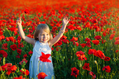 cute little girl smiles and raises her arms upwards for joy. poppy fields in Italy