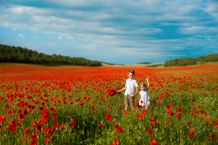 girl and boy in a field of red poppies. concept of childhood, happiness, family Stockfoto