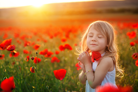 Little girl dreaming in the park. Adorable little girl girl hugs a poppy flower. Child and flowers, summer, nature and fun. Summer holidays.