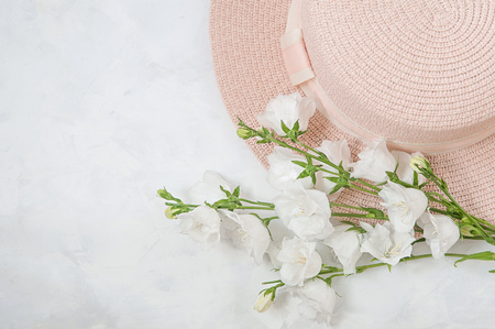 summer composition - hat, bouquet of white flowers on a white background. The concept of summer, warmth, relaxation. Stockfoto