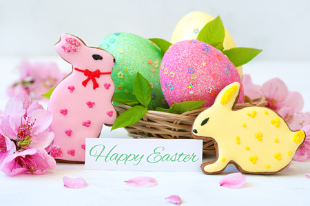 Easter Bunny and eggs. Easter eggs and flowers with bunny statuettes on wooden background