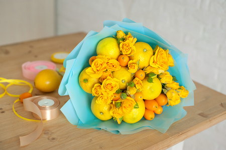 freshly made bouquet of fruit and flowers. Yellow bouquet in blue wrapper