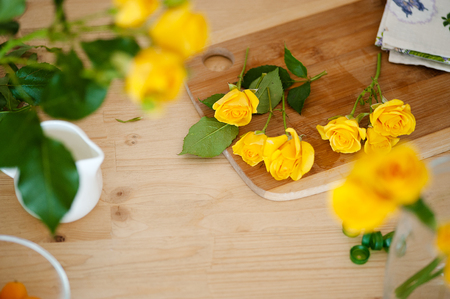 Floral flat lay composition process of making bouquet. Fresh yelow flowers on white wooden table, top view.