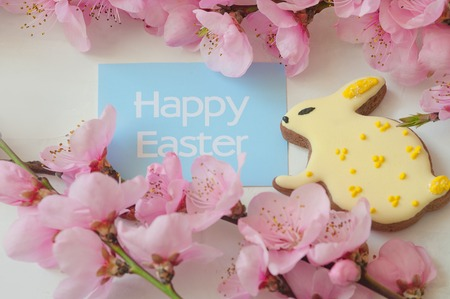 Easter greetings on a blue card, gingerbread bunny and pink flowers. Copy space. Stockfoto
