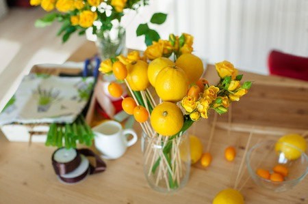 Floristics hobby. Floral and fruits bouquet making process. Overhead still life of bouquet making process
