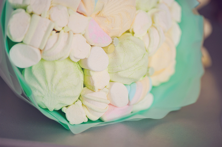 Original delicious edible bouquet consisting of candies, marshmallows and zephyrs on a white background as a gift