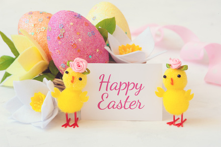 Two little yellow chicken with a congratulatory inscription - happy easter.