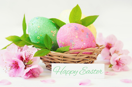 Wicker basket with Easter eggs with spring flower.