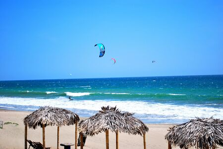 Kiteboarding on a deserted beach of Pacific coast photo