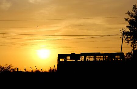Road with a silhouette of last bus on a sunset photo