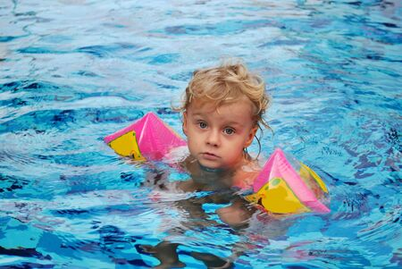 Little girl with inflatable oversleeves floats in pool photo