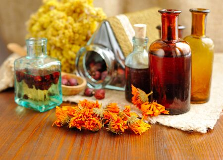 Geneeskrachtige kruiden en tincturen in flessen op zak, gedroogde bloemen, kruidengeneeskunde Stockfoto