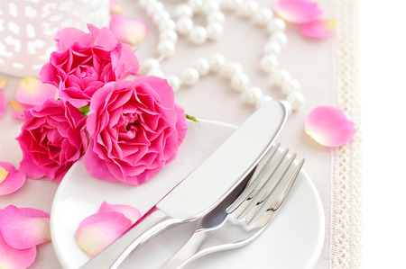 Romantic table setting with pink roses on a linen napkin photo