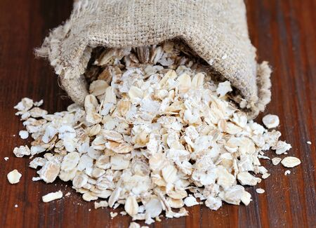 spilling: Oat flakes spilling from the burlap bag on wooden table