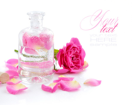 Flesje etherische olie en roze roos op wit wordt geïsoleerd Stockfoto