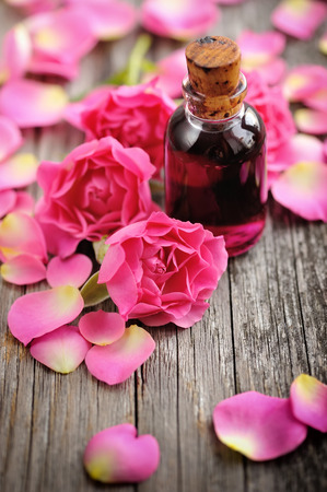 skin care products: Essential oil with rose petals on wooden background Stock Photo