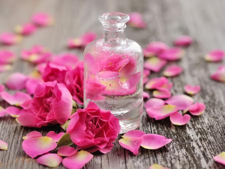 Essentiële olie met rozenblaadjes op houten achtergrond Stockfoto