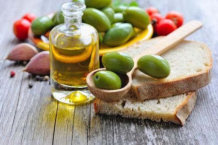 aceite de oliva: Aceitunas verdes en una cuchara de madera sobre una rebanada de pan
