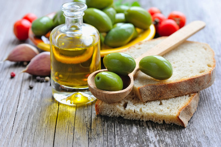 olive oil bottle: Green olives on a wooden spoon on a slice of bread