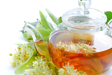 nontraditional: Teapot with linden tea and flowers, close-up Stock Photo